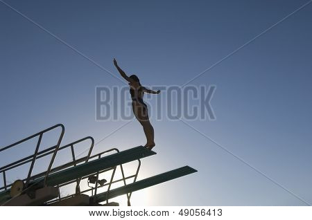 Low angle view of a female diver with arms out about to dive against the blue sky