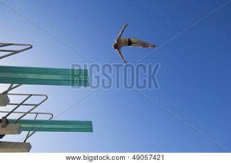 Vista de ángulo bajo de un nadador masculino preparándose para bucear desde trampolín contra el cielo azul