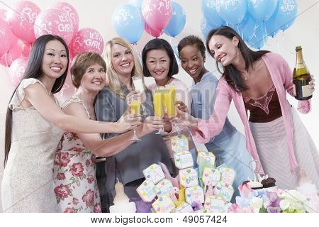 Portrait of happy multiethnic friends having a toast at baby shower