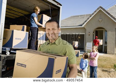 Portrait of a smiling man with box while family unloading delivery van in the background by new house