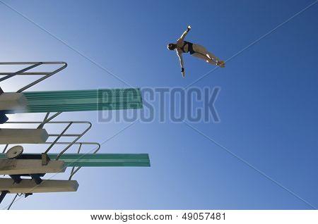 Vista de ángulo bajo de un nadador femenino prepara para bucear desde trampolín contra el cielo azul