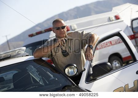 Police officer using two way radio by police car with ambulance in background