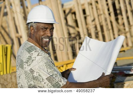 Portrait of a smiling mature man in hardhat holding blueprint in front of house construction site