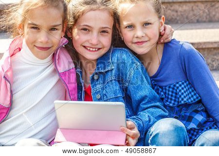 Portrait of smart basic school students with an electronic tablet