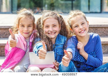 Successful school students sitting with tablet in front of a school
