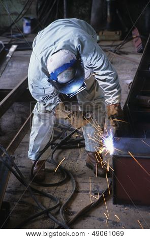 Welder bending down welding at Work