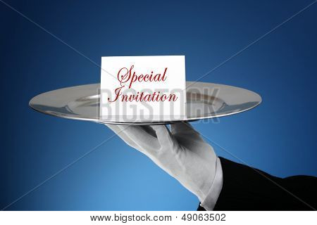 Butler or waiter holding a card reading special invitation on a silver platter- message can easily be changed