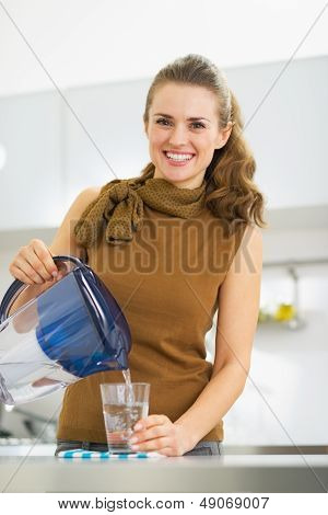 Smiling Young Housewife Pouring Water Into Glass From Water Filt