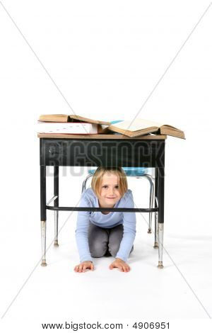 Young Girl Hiding Under A School Desk