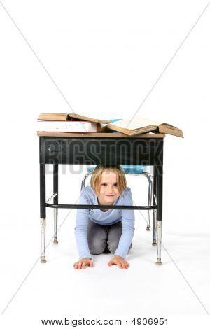 Young Girl Hiding Under A School Desk