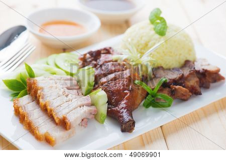 Roasted duck, roasted pork crispy siu yuk and Charsiu Chinese style, served with steamed rice on dining table. Malaysia cuisine.