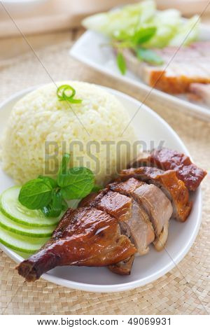 Roasted duck and roasted pork crispy siu yuk, Chinese style, served with steamed rice on dining table. Singapore cuisine.