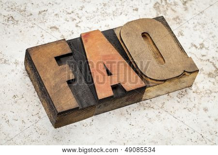 frequently asked questions - FAQ acronym - text in vintage letterpress wood type on a ceramic tile background