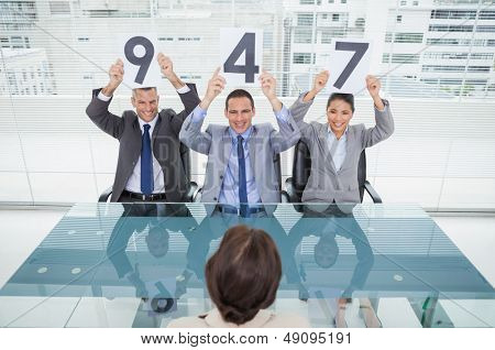 Smiling interview panel in bright office holding signs above their head giving marks to their applicant