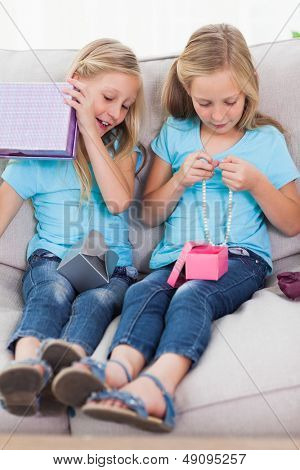 Twins unwrapping birthday gift sitting on a couch in the living room