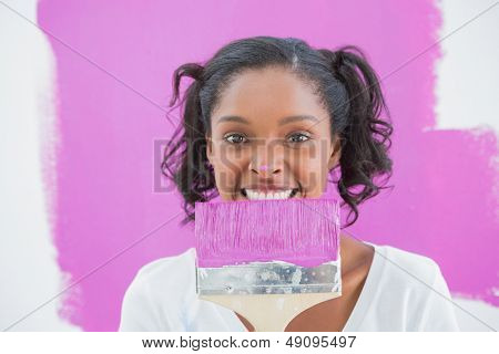 Young woman holding paintbrush with pink paint on her nose smiling at camera