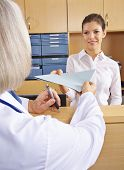 Doctor getting medical records in hospital from the receptionist