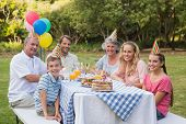 Family smiling at camera at birthday party outside at picnic table