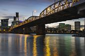 stock photo of lamp post  - Portland Oregon City Skyline Under Hawthorne Bridge by the Bank of Willamette River at Dusk - JPG