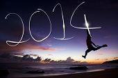 Happy New Year 2014.young Man springen en 2014 tekenen door flitslicht