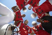 stock photo of huddle  - Low angle view of rugby players with coach forming huddle against clear sky - JPG