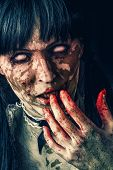 stock photo of demon  - Scary zombie woman with white eyes and bloody hand - JPG