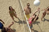 stock photo of volleyball  - Elevated view of a group of young people playing volleyball on beach - JPG