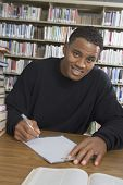stock photo of palm-reading  - Portrait of an African American male student making notes in the college library - JPG