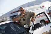stock photo of officer  - Police officer using two way radio by police car with ambulance in background - JPG
