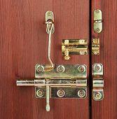 Постер, плакат: Металлические болты защелки и крючки деревянные двери крупным планом