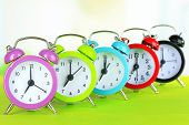 pic of early morning  - Colorful alarm clocks on table on light background - JPG
