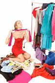 stock photo of choke  - Young woman sits near her clothes rack with lots of dressesand some clothes is on the floorand she is choking her self with her pantyhose - JPG