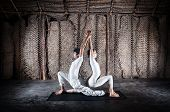 stock photo of surya  - Couple yoga of woman and man doing ashwa sanchalanasana lunge pose in white cloth in yoga hall Varkala Kerala India - JPG