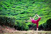 stock photo of natarajasana  - Yoga natarajasana dancer pose by woman in red cloth on tea plantations in Munnar hills Kerala India - JPG