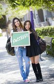 Excited Mixed Race Female Students Holding Chalkboard With Success Written on it.
