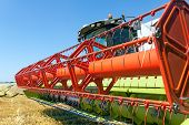 stock photo of combine  - Combine harvests wheat on a field in sunny summer day - JPG