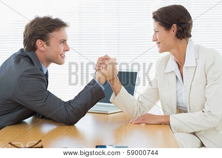 Side view of smiling young business couple arm wrestling at office desk