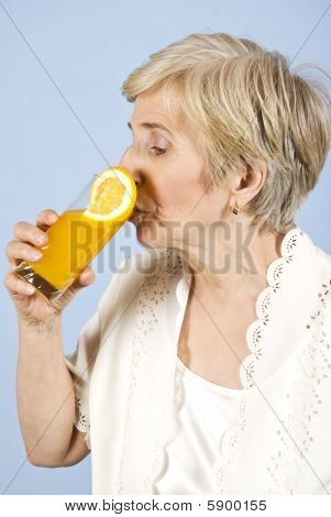 Senior Woman Drinking Fresh Orange Juice
