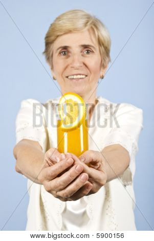 Happy Senior Woman Offer A Glass With Orange Juice