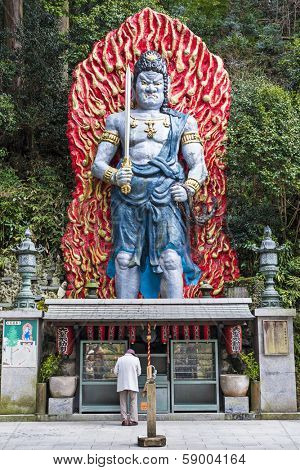 FUKUOKA, JAPAN - FEBRUARY 9, 2013: A worshiper under the large Cetaka, a god devoted to the protection from disaster.