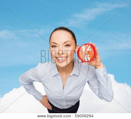 business, time and deadline concept - smiling businesswoman with red clock