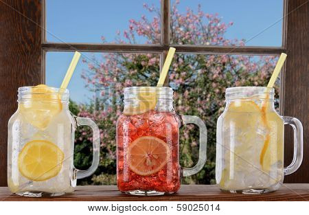 Glasses of lemonade and fruit Juice on a window ledge on a bright sunny summer day. The mason jar style glasses have handles and drinking straws. Thru the window is a tree and blue sky.