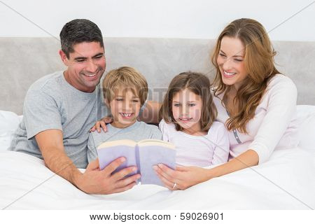 Smiling family reading storybook in bed