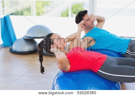 Side view of a fit young couple exercising on fitness balls at a bright gym