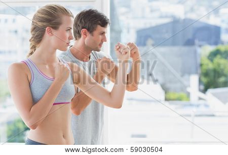 Side view of a serious young couple standing in boxing stance in fitness studio
