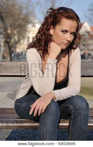 Young Sad Woman Siting On Bench In Town