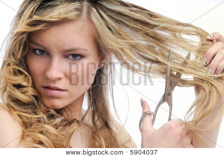 Unhappy Young Woman Cutting Hair With Scissors