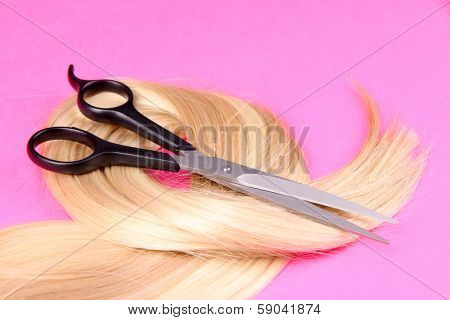 Long blond hair with scissors on pink background