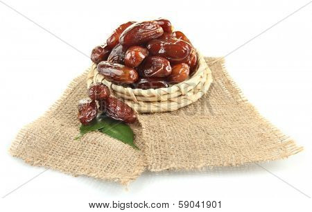 Dried dates on wicker stand sackcloth isolated on white