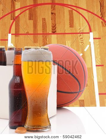 A Basketball Six Pack of Beer Bottles and a Glass of Ale on a white table top with Court in background. Great for NBA or March Madness themed projects.